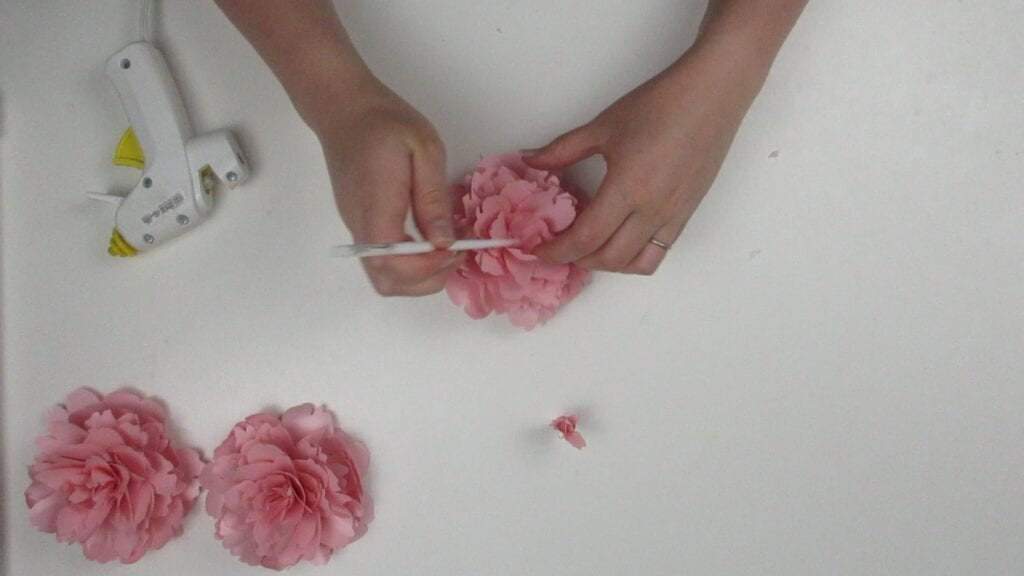 using a paintbrush to glue the peony together