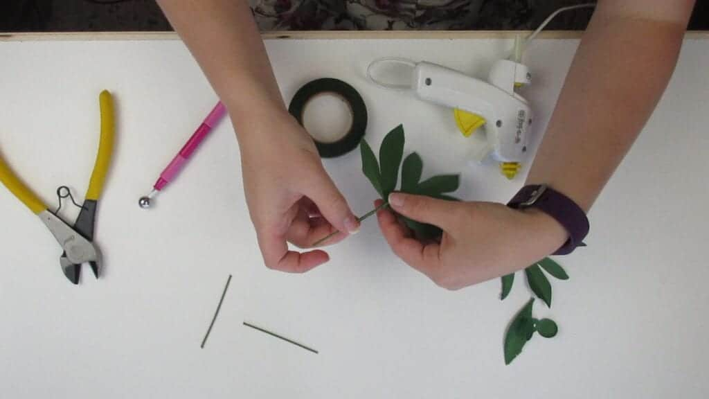 gluing the leaves of the paper peony to the wire