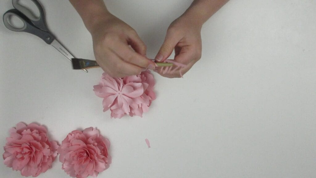 Curling the center of the paper peony with a paintbrush